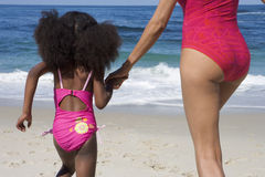 Mother and daughter (5-7) holding hands near water's edge on sandy beach, mid-section, rear view royalty free stock image