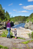 Mother and daughter holding hands standing near waterfall at summer Stock Photography