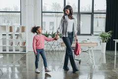 Mother and daughter holding hands while walking in modern office Royalty Free Stock Photo
