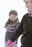 Mother and daughter holding hands in winter setting.  Royalty Free Stock Photography