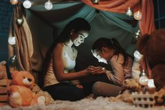Mother and Daughter is Holding a Light in Hands. Mother and Daughter Lying on Carpet. Persons Lying Under the Fake Tent. Mother is Showing a Light in Hands to stock images