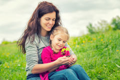Mother and daughter holding little green plant in hands Stock Images