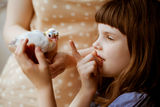 Mother and daughter holding little  pigeon. Consept of innocence Stock Images