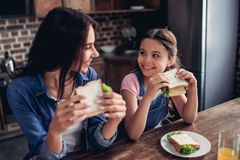 Mother and daughter holding sandwiches stock images