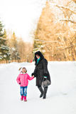Mother and daughter holding their hands outdoors. In winter Stock Image