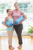 Mother and daughter holding yoga mats. At home in the living room Royalty Free Stock Photos