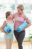 Mother and daughter holding yoga mats. At home in the living room Royalty Free Stock Image