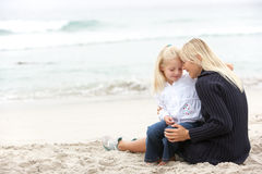 Mother And Daughter On Holiday Sitting On Beach Stock Image