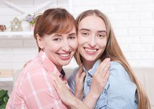 Mother and daughter at home background. Smiling women. Early pregnancy. Mother day. Woman nature beauty. Mother and daughter at home background. Smiling women Royalty Free Stock Image