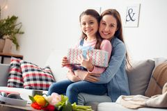 Mother and daughter at home birthday sitting mother hugging daughter holding gift box smiling happy stock image