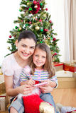 Mother and daughter at home at Christmas Stock Photos
