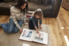 Mother And Daughter At Home Looking Through Photo Album Stock Image