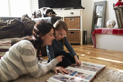 Mother And Daughter At Home Looking Through Photo Album Royalty Free Stock Photography