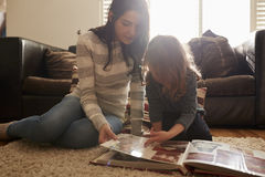Mother And Daughter At Home Looking Through Photo Album royalty free stock photos