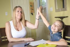 Mother and daughter at home. Mom teachs little girl homework. Stock Photo