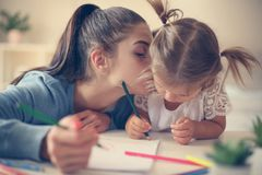 Mother teaching her daughter to drawing. Mother and daughter at home. Mother teaching her daughter to drawing and writing royalty free stock photos