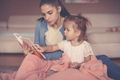 Mother and daughter at home sitting on floor and reading bo royalty free stock photography