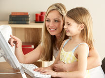 Mother And Daughter At Home Using Computer Stock Images