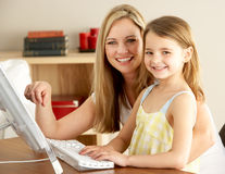 Mother And Daughter At Home Using Computer Royalty Free Stock Photos