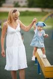 Mother with daughter on horizontal bar balance Stock Photos
