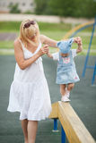 Mother with daughter on horizontal bar balance Royalty Free Stock Image