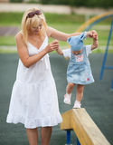 Mother with daughter on horizontal bar balance Royalty Free Stock Images