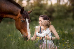 Mother and daughter with  horse. Walking on summer field Stock Photo