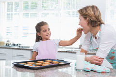 Mother and daughter with hot fresh cookies Stock Photos