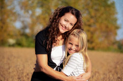 Mother and daughter hug. Mom and daughter hugging in a country field stock photos