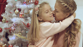Mother and daughter hug and kiss each other near a Christmas tree. Mother and daughter hug and kiss each other near the Christmas tree stock photos
