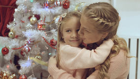 Mother and daughter hug and kiss each other near a Christmas tree. Mother and daughter hug and kiss each other near the Christmas tree stock photography