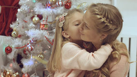 Mother and daughter hug and kiss each other near a Christmas tree. Mother and daughter hug and kiss each other near the Christmas tree stock photo