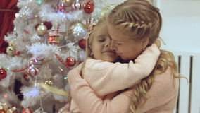Mother and daughter hug and kiss each other near a Christmas tree. Mother and daughter hug and kiss each other near the Christmas tree royalty free stock images