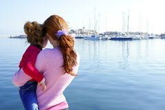 Mother and daughter hug looking blue marina Stock Image