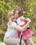 Mother and daughter hug in park with scooter royalty free stock photo