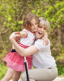 Mother and daughter hug in park with scooter stock photos