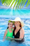 Mother and daughter hug in pool tropical beach. Caribbean background stock image