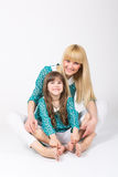 Mother and daughter hug sitting wearing matching outfit. Beautiful blonde mother and brunet five year old daughter hug sitting wearing matching outfit smiling stock photography