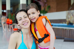 Mother and daughter hug after swimming. Happy wet mother and little daughter hug after swimming in pool royalty free stock image
