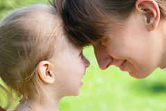 Mother and daughter hugged each other foreheads. Mother and daughter hugged each other at loggerheads, look in the eyes Royalty Free Stock Photos