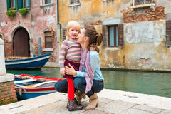 Mother and daughter hugging and cuddling near canal in Venice Stock Photo