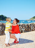 Mother and daughter hugging in front of lagoon with yachts Stock Photo