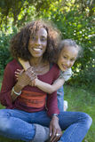 Mother and daughter hugging on grass Stock Images