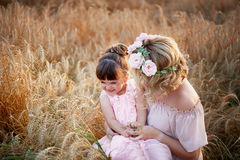 Mother and daughter hugging on her head a garland of roses, soft image royalty free stock image