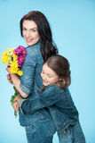 Mother and daughter hugging and holding flowers in studio on blue, Happy mothers day Stock Photos