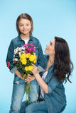 Mother and daughter hugging and holding flowers in studio on blue, Happy mothers day Stock Images