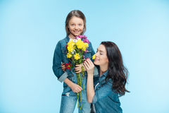 Mother and daughter hugging and holding flowers in studio on blue, Happy mothers day Royalty Free Stock Image