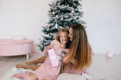 Mother and daughter hugging at home near Christmas tree. woman and girl with a Christmas present Stock Photo