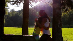 Mother and daughter hugging and kissing on tree log. Sunset in the background.  stock footage
