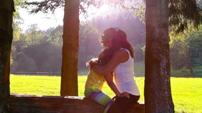 Mother and daughter hugging and kissing on tree log. Sunset in the background.  stock video
